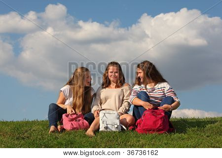 Three girls with bags chat and laugh at green grass at background of blue sky.