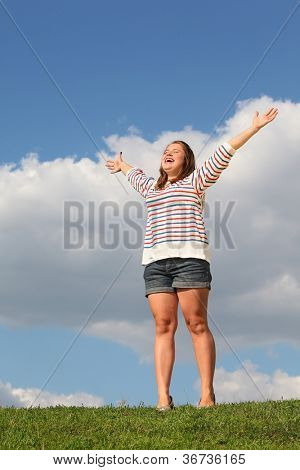 Young fat girl stands at green grass, raises her hands and laughs at background of blue sky.