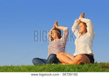 Two young girls meditate at green grass at background of blue sky.