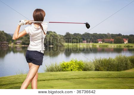 Girl golf player teeing-off from tee-box with driver, view from behind.