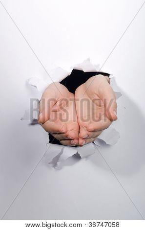 Mãos através do furo no papel