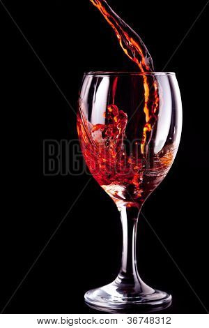 Empty glass being filled with wine against black background