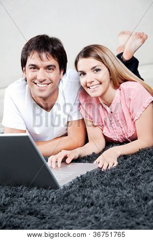 Happy young couple using laptop, looking at camera.