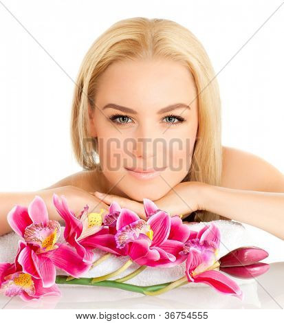 Closeup portrait of attractive female with pink orchid flower, pretty woman with natural makeup isolated on white background, young lady relaxed in luxury spa salon, alternative therapy concept