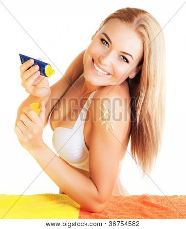Photo of cheerful pretty female apply suntan cream, young lady holding bottle with tanning cream isolated on white background, girl wearing beach bikini, facial cosmetics, health and beauty care