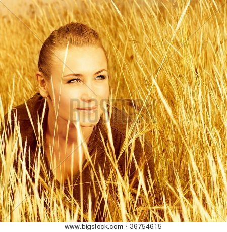 Picture of pretty woman sitting on wheat field, closeup portrait of cute young lady on golden ryes background, autumn harvest concept, happy beautiful girl enjoying cereal meadow, fall season