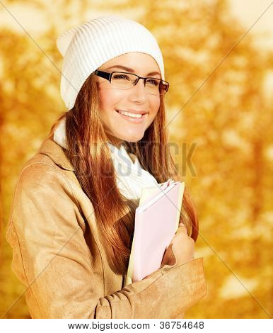 Closeup portrait of pretty student girl in autumn park, adult schoolgirl enjoying education, beautiful teen holding books, stylish female wearing hat with scarf and glasses, back to school
