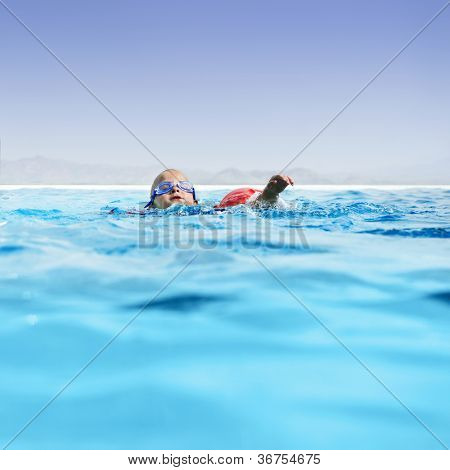 Young boy learning to swim in an luxurious infinity pool.