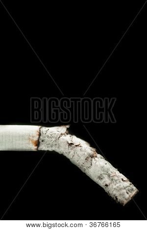 Cinder of cigarette against a black backgrouns