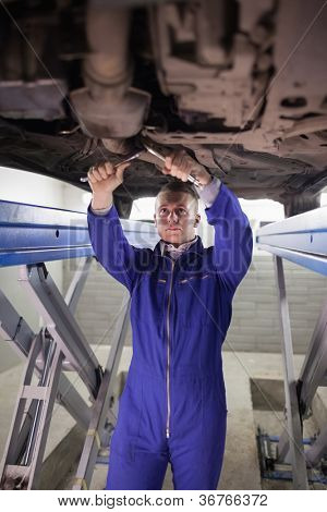 Concentrated mechanic repairing a car with spanners in a garage