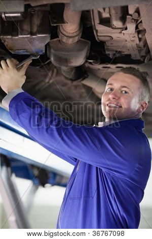 Smiling mechanic repairing a car in a garage