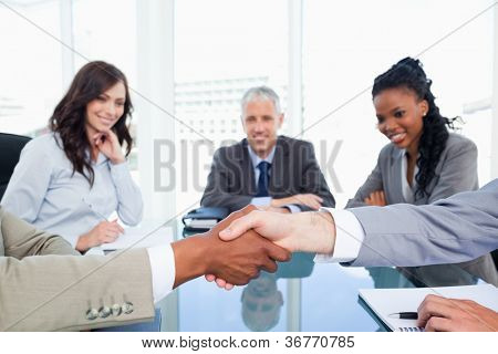 Mitarbeiter Händeschütteln während deren Direktor und zwei Führungskräfte beobachten