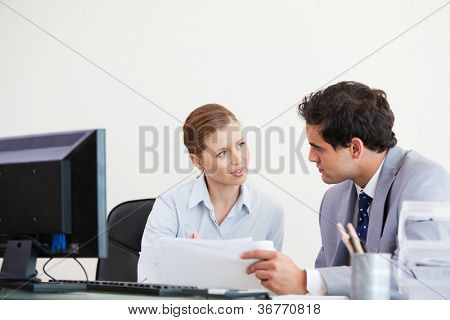 Colleagues talking while holding a sheet against grey background