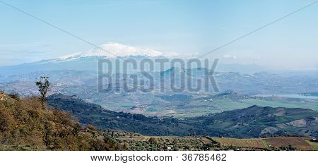 Sicilian rural landscape in winter with snow peak of Etna volcano in Italy