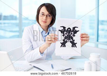 Psicólogo grave mostrando el papel con tinta de Rorschach