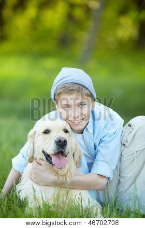 Portrait of cute lad embracing his fluffy friend and looking at camera