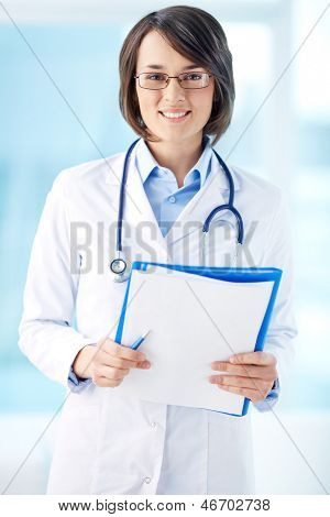 Vertical portrait of a lovely general practitioner holding papers