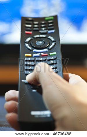Mão com controle remoto de televisão