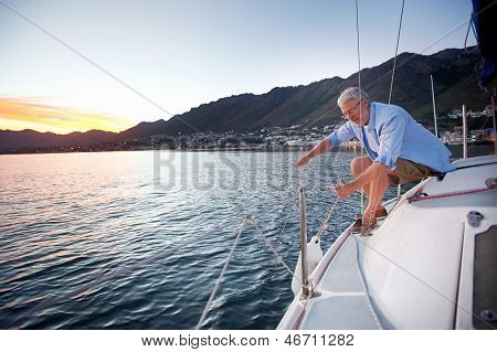 mature retired man sailing his boat as a hobby at sunrise