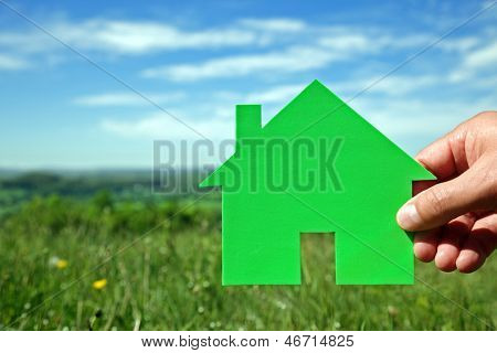 Real estate housing development concept hand holding green house symbol in a field