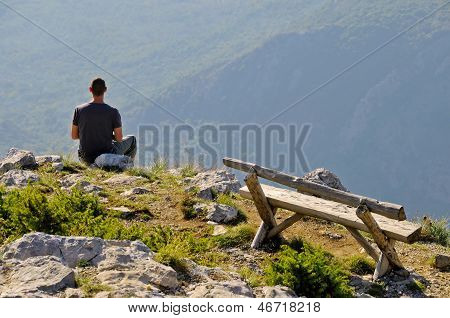 Man sitting on top of the hill