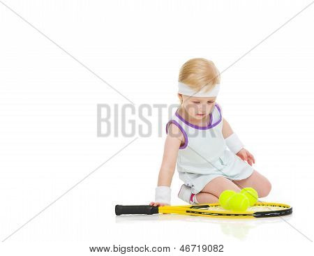 Baby In Tennis Clothes With Racket And Balls