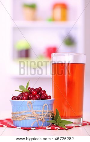 Glass of cranberry juice and ripe red cranberries in bowl on table
