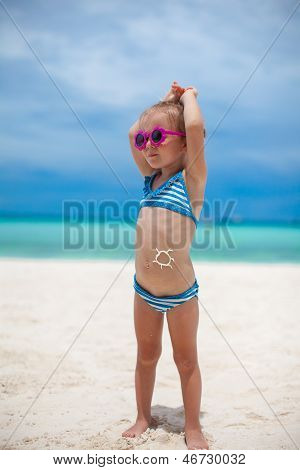 Little Girl On Her Stomach Painted A Smile By Sun Cream