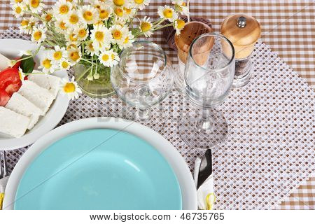 Table setting with chamomiles on checkered tablecloth