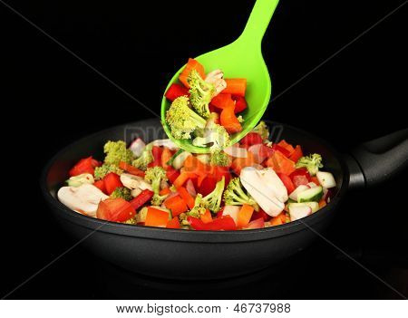 Vegetable ragout in pan, isolated on black