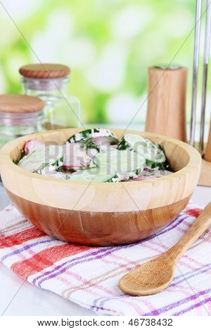 Vitamin vegetable salad in wooden bowl on wooden table on natural background