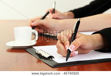 Close up of businesswoman hands  with cup of coffee during teamwork