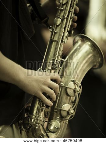 jazz band playing on the street, selective focus on the hands with sax