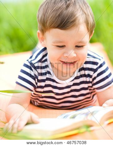 Little boy is reading book, outdoor shoot