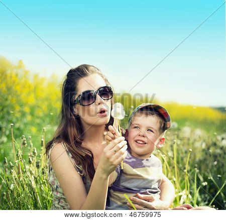 Mom and her son blowing off dandelion