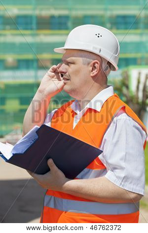 Construction engineer with folder near the scaffolding