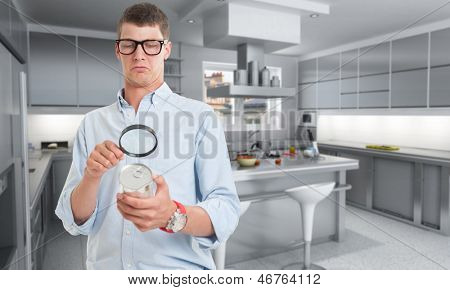 Young man examining a can through a magnifying glass in a kitchen
