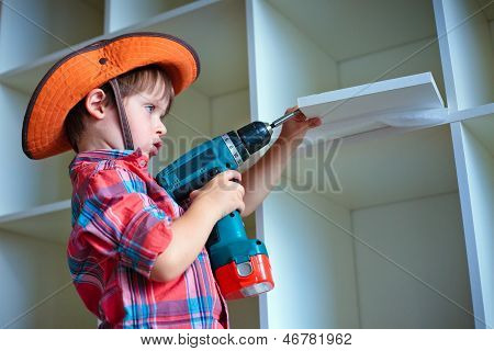 Cute little boy using an electric screwdriver