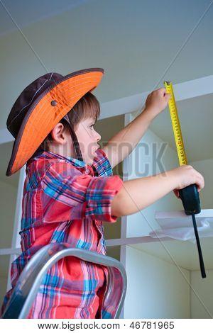 Cute little boy measuring a part of cupboard