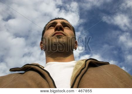 Man Looking Up With The Clouds On The Background