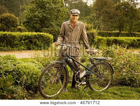 Young man posing with retro motorbike in the park. Vintage style.