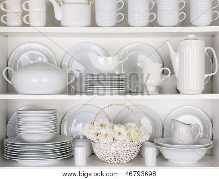 Closeup of white plates and dinnerware in a cupboard. A basket of white roses is centered on the bottom shelf. Items include, plates, coffee cups, saucers, soup tureen, tea pot, and gray boats.
