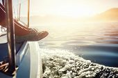 stock photo of sailing vessel  - feet on boat sailing at sunrise lifestyle - JPG