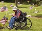 stock photo of cemetery  - disabled man in a wheelchair visits a fallen brother at the cemetery - JPG