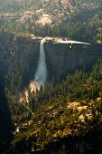 image of hang-gliding  - Hang glider soars high over waterfall and forest in Yosemite National Park USA - JPG