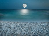 image of moonlight  - Pebble beach in the the night wit clear sky with stars lit by the full Moon just above horizon - JPG