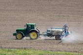 stock photo of tractor  - Tractor fertilizes the field detailed side view - JPG