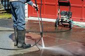 image of denim jeans  - A man wearing rubber boots is pressure washing a drive way - JPG