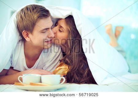Desfrutando de um outro ao mesmo tempo tomando café da manhã na cama de casal