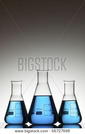 tres frascos con fondo azul y blanco líquido